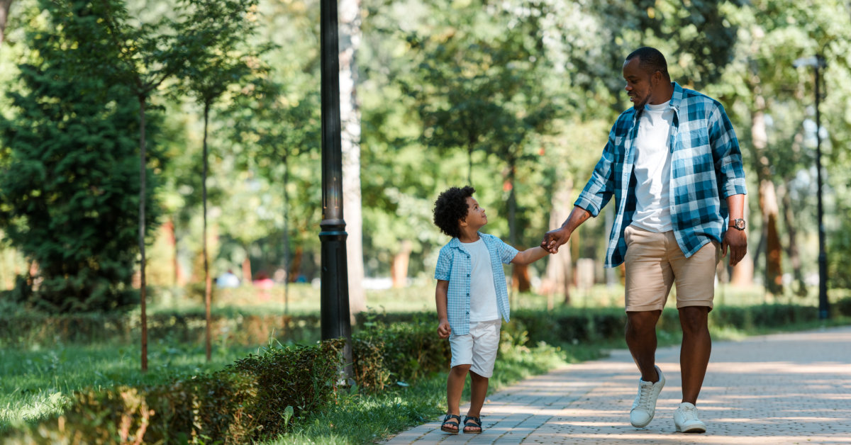 Father and son walking through the park