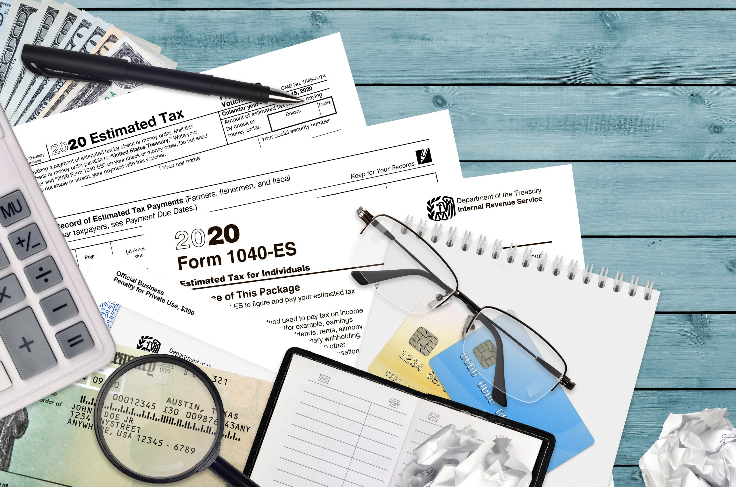 Tax paperwork with glasses and magnifying glass